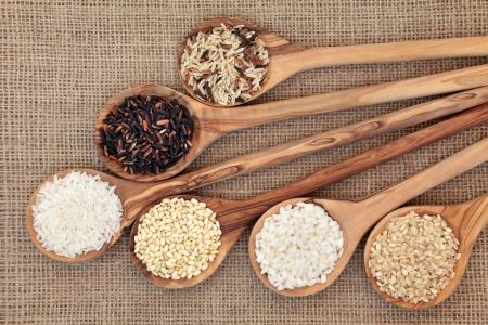 Rijstsoorten in olijfhout lepels over juteachtergrond