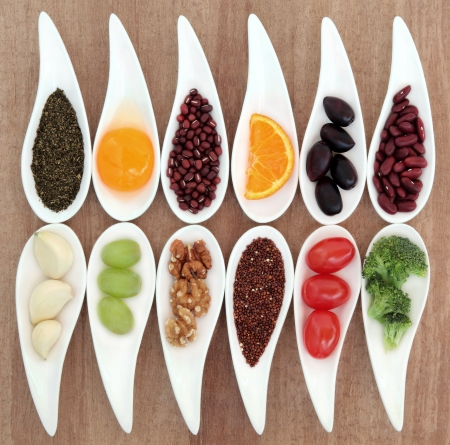 Healthy super food selection in white porcelain dishes over papyrus background