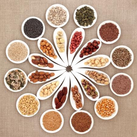 sementi: Dado grande e selezione di cibo di semi in porcellana ciotole su sfondo della tela di iuta Archivio Fotografico
