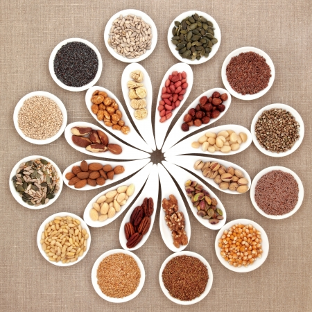 Large nut and seed food selection in porcelain bowls over hessian background