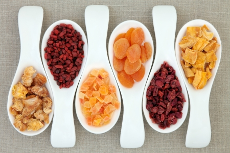 papaw: Dried fruit in white porcelain scoops over hessian background  Stock Photo