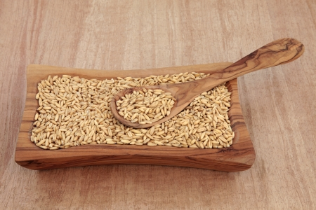 groat: Oat groats in an olive wood bowl with spoon over papyrus background  Stock Photo