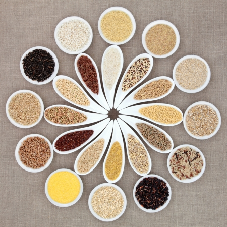 groat: Large grain and cereal food selection in white porcelain bowls over hessian background  Stock Photo