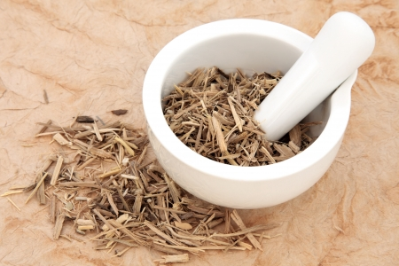 chinese herbal medicine: Ginseng root herb in a mortar with pestle and loose over papyrus background  Stock Photo