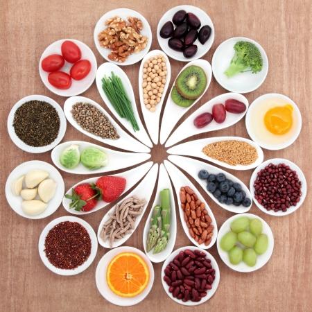 gezondheid: Grote health food selectie in witte porseleinen kommen en schotels over papyrusachtergrond Stockfoto