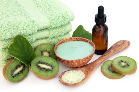 moisturiser: Aromatherapy skincare treatment with essential oil, moisturiser, kiwi fruit, green towels and bath crystals over white background  Stock Photo