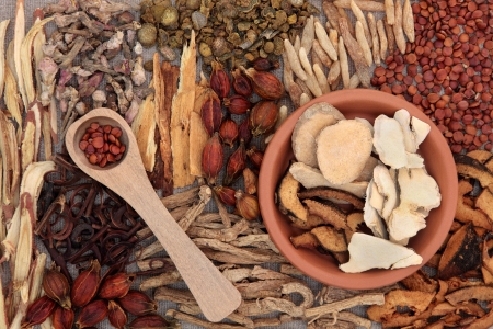 Traditional chinese herbal medicine ingredients over hessian background  photo