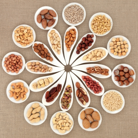 Large nut selection in white porcelain dishes over hessian background  photo
