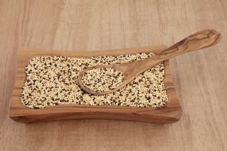 tricolour: Tricolour quinoa grain in an olive wood bowl with spoon over papyrus background