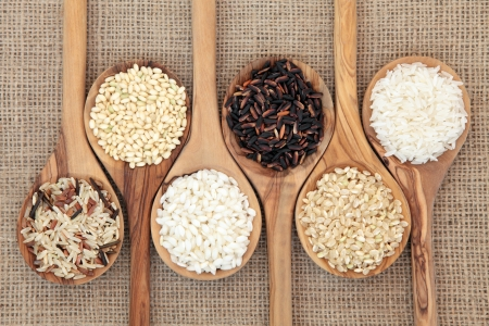 arroz blanco: Las variedades de arroz en las cucharas de madera de olivo sobre fondo de arpillera