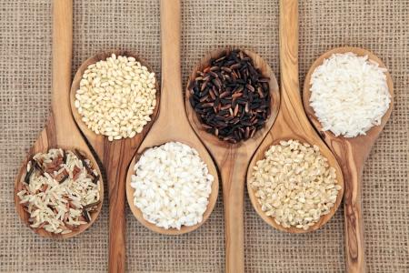 Rice varieties in olive wood spoons over hessian background    Stock fotó