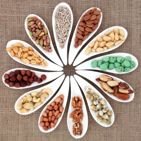 Nut selection in white porcelain dishes over hessian background  photo