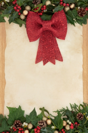 Christmas border decoration with red bow, holly, ivy and mistletoe on old parchment paper and oak background  photo