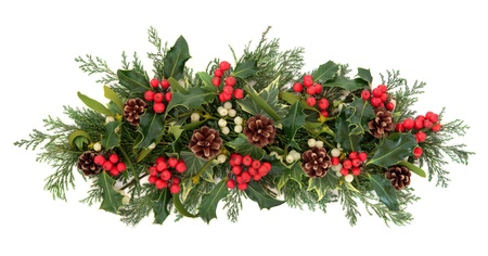 christmas ivy: Christmas floral decoration with holly, ivy, mistletoe, pinecones and winter greenery over white background