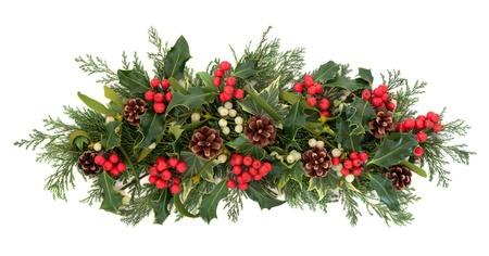 Kerst florale decoratie met hulst, klimop, maretak, dennenappels en winter groen over witte achtergrond Stockfoto