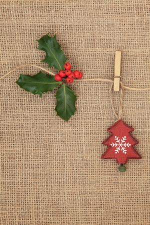 Christmas tree decoration with holly berry sprig hanging on a line over hessian background  photo