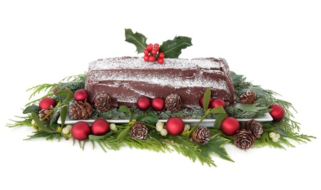 yule: Christmas chocolate yule log cake with red bauble decorations, holly, mistletoe, snow, pinecones and winter greenery over white background