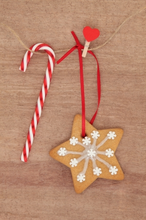 Christmas gingerbread snowflake cookie hanging on a line with rock cane candy bar Stock Photo - 21539863