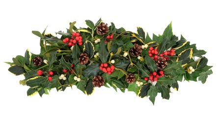 christmas ivy: Christmas floral arrangement with holly, ivy, mistletoe, pine cones and winter greenery over white background  Stock Photo