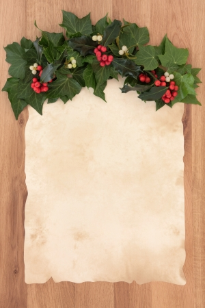 Christmas parchment blank letter with border of holly, ivy and mistletoe over oak background  photo