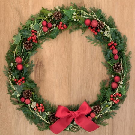 pine wreath: Christmas floral wreath decoration with baubles, red bow, holly and winter greenery over oak background