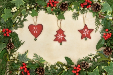 Christmas floral border with wooden bauble decorations, holly, ivy and mistletoe on old parchment paper background