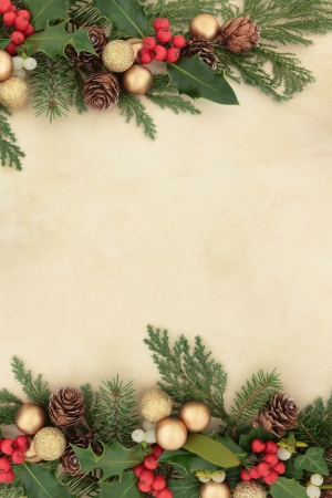 Christmas and winter border with gold baubles, natural holly, mistletoe, ivy, fir leaf sprigs and pine cones over parchment background  photo