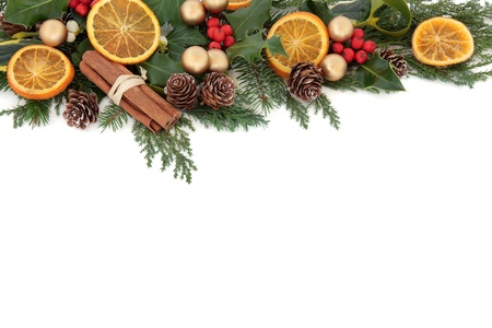 Christmas floral border with dried orange fruit and cinnamon spice, baubles and winter greenery over white background
