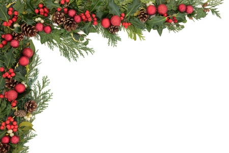 Christmas border with red baubles, holly, mistletoe, ivy and winter greenery over white background  photo