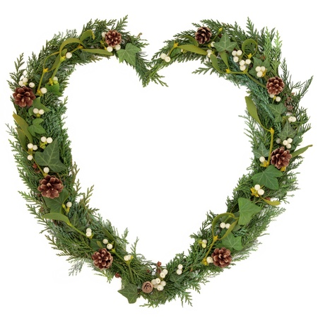 Christmas heart shaped floral wreath with mistletoe, ivy, fir and pine cones over white background   Фото со стока