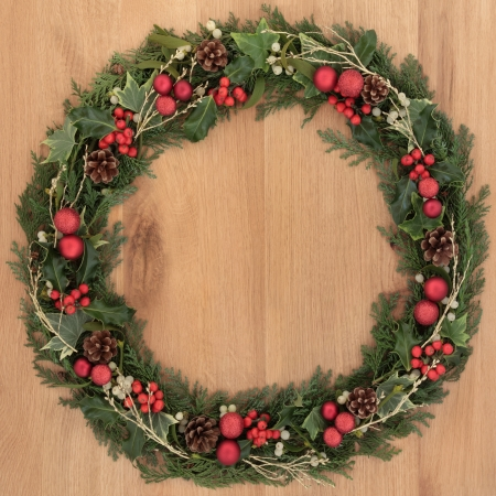 Christmas wreath with red bauble decorations, holly, mistletoe, ivy, pine cones and cedar over oak background  photo