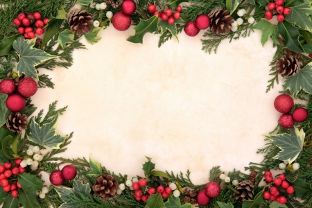 Christmas floral border with red bauble decorations, holly, ivy and mistletoe over old parhcment background