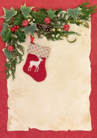 Christmas eve reindeer stocking with border of winter greenery and red bells over old parchment and red background   photo