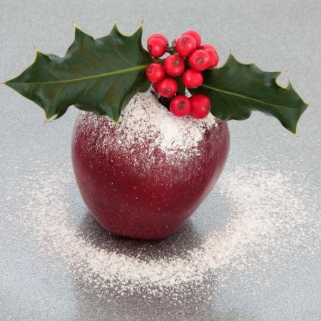 christmas apple: Mela di Natale con agrifoglio, bacche rosse e la neve glassa spolvero su sfondo argento