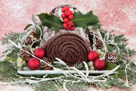 yule log: Christmas chocolate yule log cake with red bauble decorations, holly, mistletoe, snow, pine cones and winter greenery