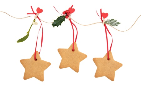 Christmas star gingerbread cookies hanging on a line with holly, mistletoe and fir leaf sprigs over white background      photo