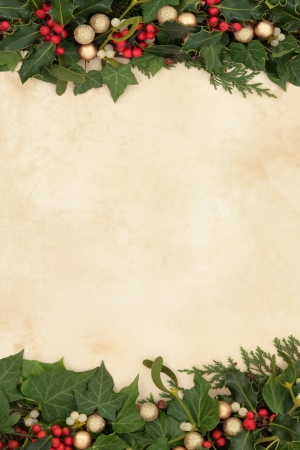 Christmas floral background border with gold baubles, holly, ivy and mistletoe on old parchment paper  photo
