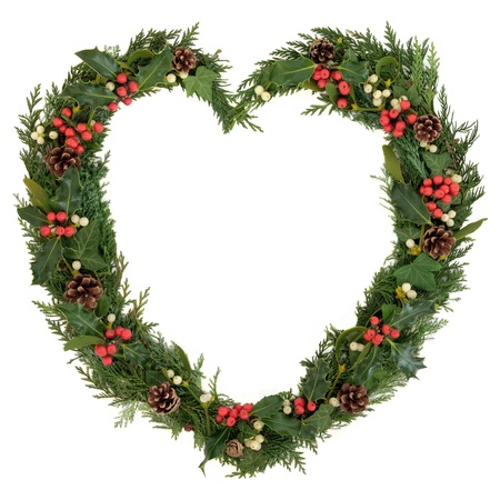 Christmas heart wreath with holly, mistletoe, ivy, pine cones and cedar leaf sprigs over white background  photo