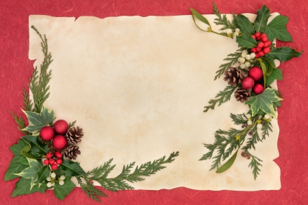 Christmas background border with red baubles, holly, mistletoe, ivy  and winter greenery over parchment and red paper  photo