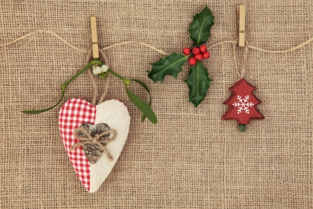 Christmas tree decorations with mistletoe and holly berry sprig over hessian background  photo