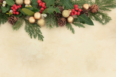 Christmas background border with gold baubles, natural holly, mistletoe, ivy, fir leaf sprigs and pine cones over parchment  photo