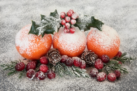 fir cones:  Christmas cranberry and mandarin orange fruit decoration with snow, holly, fir and pine cones