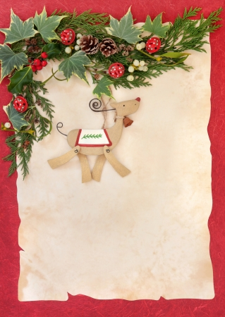 Christmas floral border with retro wooden dog bauble, red bells, holly, mistletoe and winter greenery over parchment and red background  photo