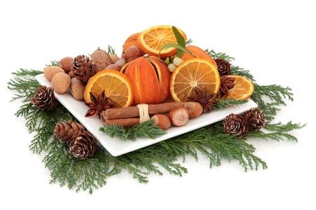 muerdago: Disposición de alimentos de Navidad con frutas secas de naranja, frutos secos, especias y el invierno verde sobre fondo blanco