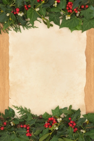 Christmas background border with holly, ivy and mistletoe on old parchment paper over oak  photo