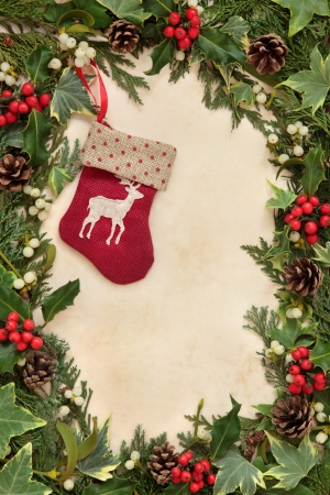 Christmas eve border with red reindeer stocking, holly, ivy and mistletoe over old parchment paper  photo