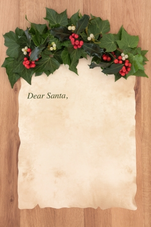 Letter to santa claus on old parchment paper with border of holly, ivy and mistletoe over oak background  photo