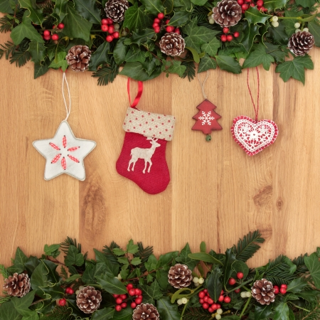 Christmas eve symbols of red stocking, tree, star and heart, with holly, ivy and mistletoe over oak background  photo