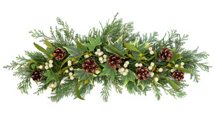 Christmas floral decoration with mistletoe, ivy pine cones and winter greenery over white background