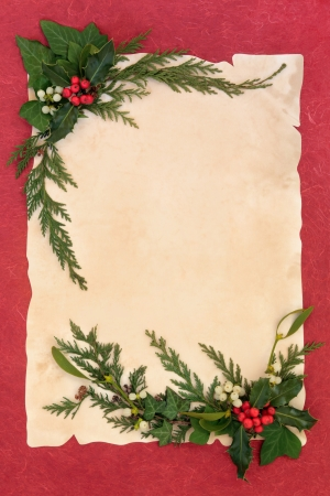 Christmas decorative border with holly, mistletoe, ivy and cedar leaf sprigs over old parchment and red mottled background  photo